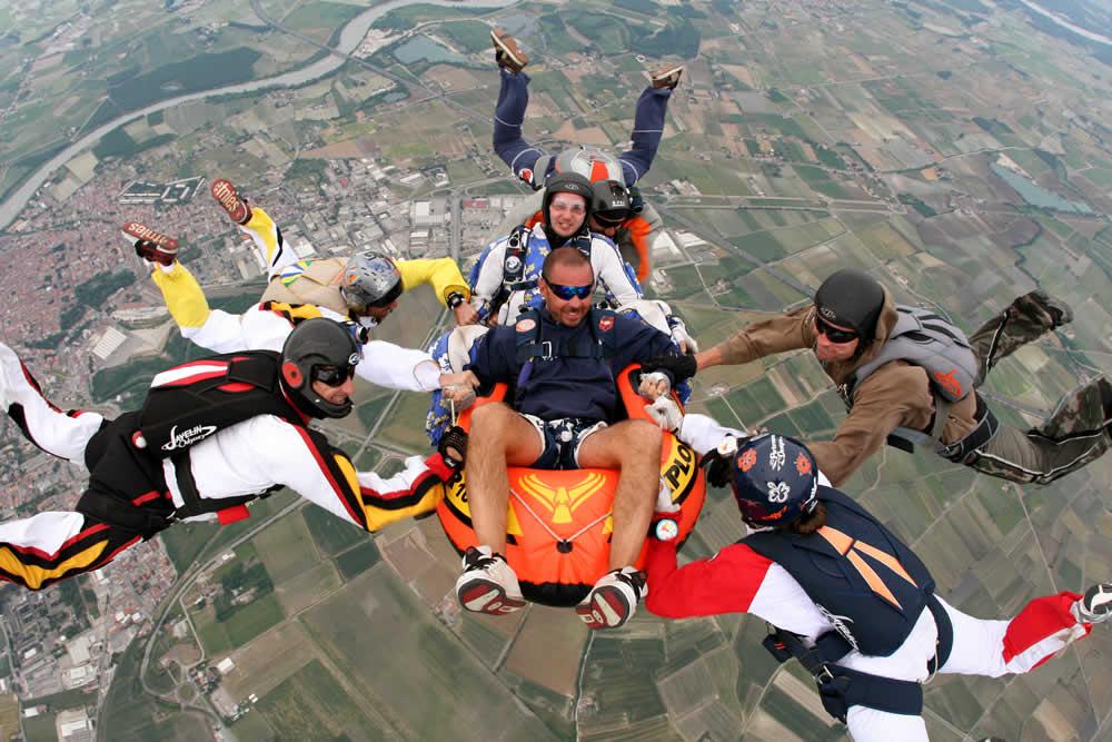 In volo con il canotto per festeggiare il compleanno di Carlo Rizzi, il paracadutista al centro dell'immagine