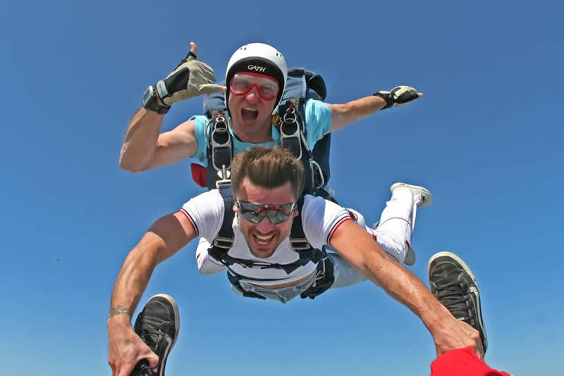 Un lancio con paracadute tandem durante la caduta libera, dove il passeggero tandem prende i piedi del videoperatore