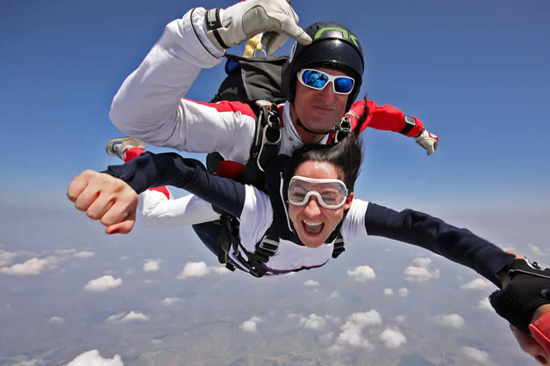 Immagine di un lancio con paracadute tandem in cui la passeggera tandem ride e si diverte