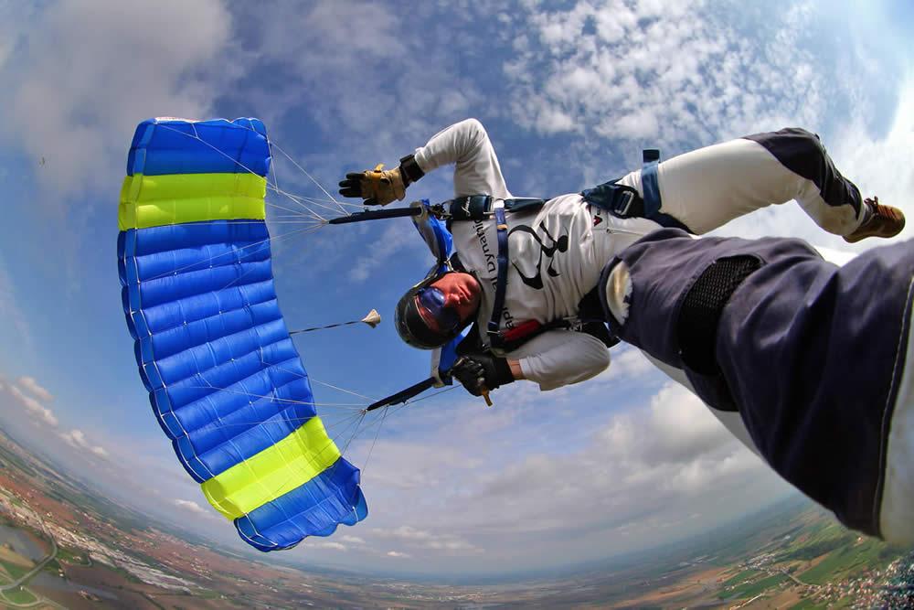 Un paracadutista durante la discesa col paracadute durante una virata sulla città di Casale Monferrato, con alle spalle il territorio della Lombardia